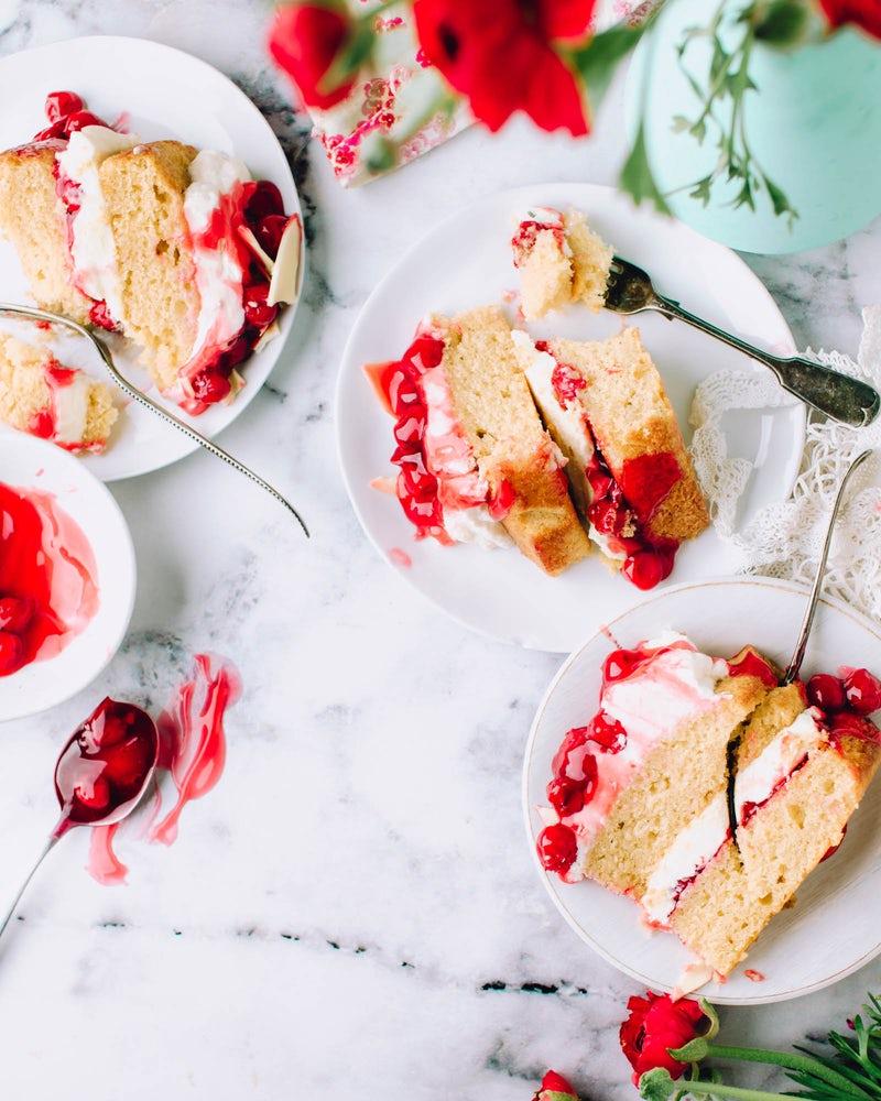 sliced cakes beside stainless steel forks on round white ceramic plates